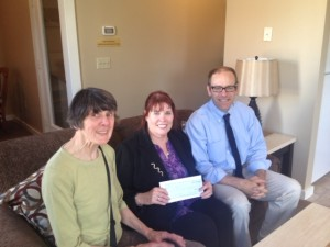 Christine Tattersall and Rob Mitchell present Marble Valley Runners check to Marianne Kennedy, Executive Director